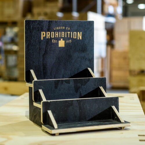 Prohibition Liquor Co router cut, tiered bar display with logo laser etched out of black laminated ply